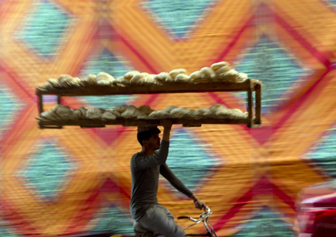 A vendor carries bread tray over his bicycle, in Cairo, Egypt, on March 3, 2017. (AP Photo/Amr Nabil)