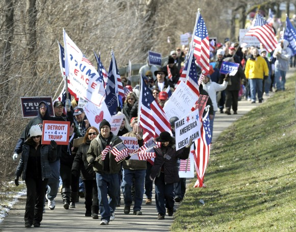 Trump supporters march east on the bike path along Metro Parkway in Clinton Township, Mich. on March 4, 2017. (Todd McInturf /Detroit News via AP)