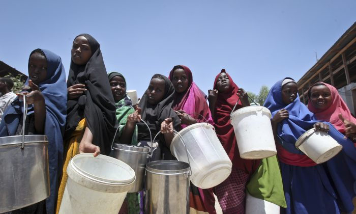 Displaced Somali girls who fled the drought in southern Somalia stand in a queue to receive food handouts at a feeding center in a camp in Mogadishu, Somalia, in this file photo. (AP Photo/Farah Abdi Warsameh, File)