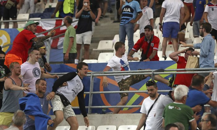 Russian supporters attack an England fan at the end of the Euro 2016 Group B soccer match between England and Russia, at the Velodrome stadium in Marseille, France on June 11, 2016. A Russian lawmaker has proposed an unorthodox solution to the country's football hooliganism woes ahead of next year's World Cup, legalize it and turn it into a spectator sport. (AP Photo/Thanassis Stavrakis, File)