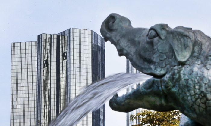A small dragon sculpture on a fountain with the headquarters of the Deutsche Bank in background in Frankfurt, Germany on Oct. 11, 2016. (AP Photo/Michael Probst,file)