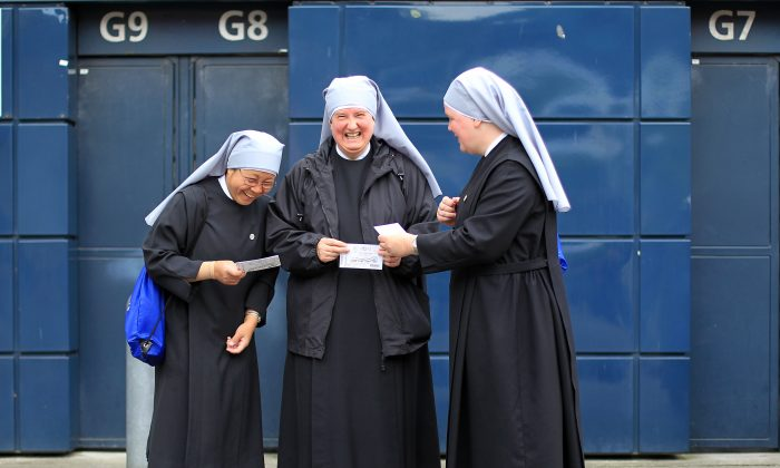 Catholic nuns laugh as they attend the closing ceremony with around 80,000 pilgrims of the 50th International Eucharistic Congress at Croke Park in Dublin, Ireland on June 17, 2012.   Pilgrims from more than 120 countries are attending the Congress which is an international gathering held every four years.  The Eucharistic Congress organized by the Vatican every four years in a different part of the world begun in the 19th century. It highlights the Catholic Church?s belief in transubstantiation, the idea that bread and wine transforms during Mass into the actual body and blood of Jesus Christ. AFP PHOTO/ PETER MUHLY        (Photo credit should read PETER MUHLY/AFP/GettyImages)