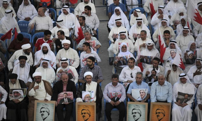 Leaders of opposition groups, including Sheik Ali Salman, head of the largest Shiite Muslim opposition society Al Wefaq, front row fourth left, participates with thousands of Bahrainis carrying national flags and posters of jailed political and religious opposition figures in a rally in Muqsha, Bahrain on Sept. 20, 2013. (AP Photo/Hasan Jamali, File)