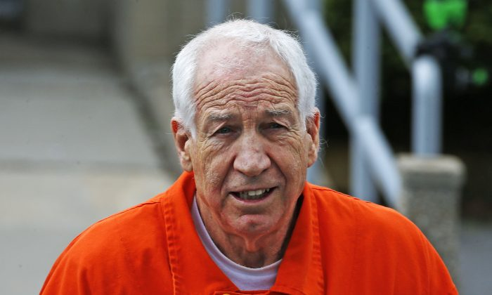 Former Penn State University assistant football coach Jerry Sandusky leaves the Centre County Courthouse after a hearing of arguments on his request for an evidentiary hearing as he seeks a new trial in Bellefonte, Pa., in this file photo. (AP Photo/Gene J. Puskar)