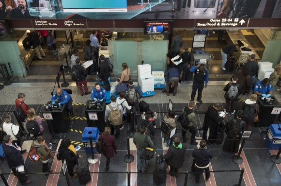 Travelers wait in line at a security screening checkpoint inside the airport terminal at Ronald Reagan Washington National Airport in Arlington, Virginia, on Dec. 22, 2016. (SAUL LOEB/AFP/Getty Images)
