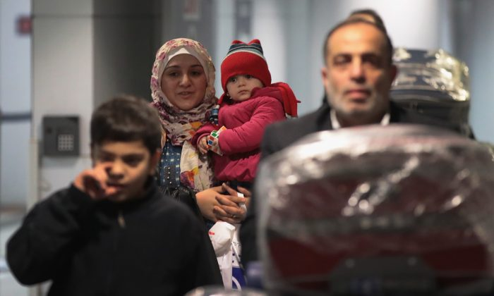 Syrian refugee Baraa Haj Khalaf clutches her daughter Shams as they get through customs at O'Hare Airport in Chicago on a flight from Istanbul, Turkey, on Feb. 7, 2017. (Scott Olson/Getty Images)
