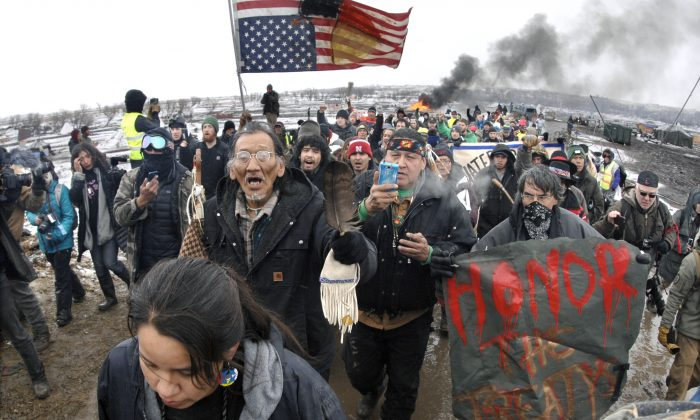A large crowd representing a majority of the remaining Dakota Access Pipeline protesters march out of the Oceti Sakowin camp before the 2 p.m. local time deadline set for evacuation of the camp mandated by the U.S. Army Corps of Engineers near Cannon Ball, N.D. (Mike McCleary/The Bismarck Tribune via AP)