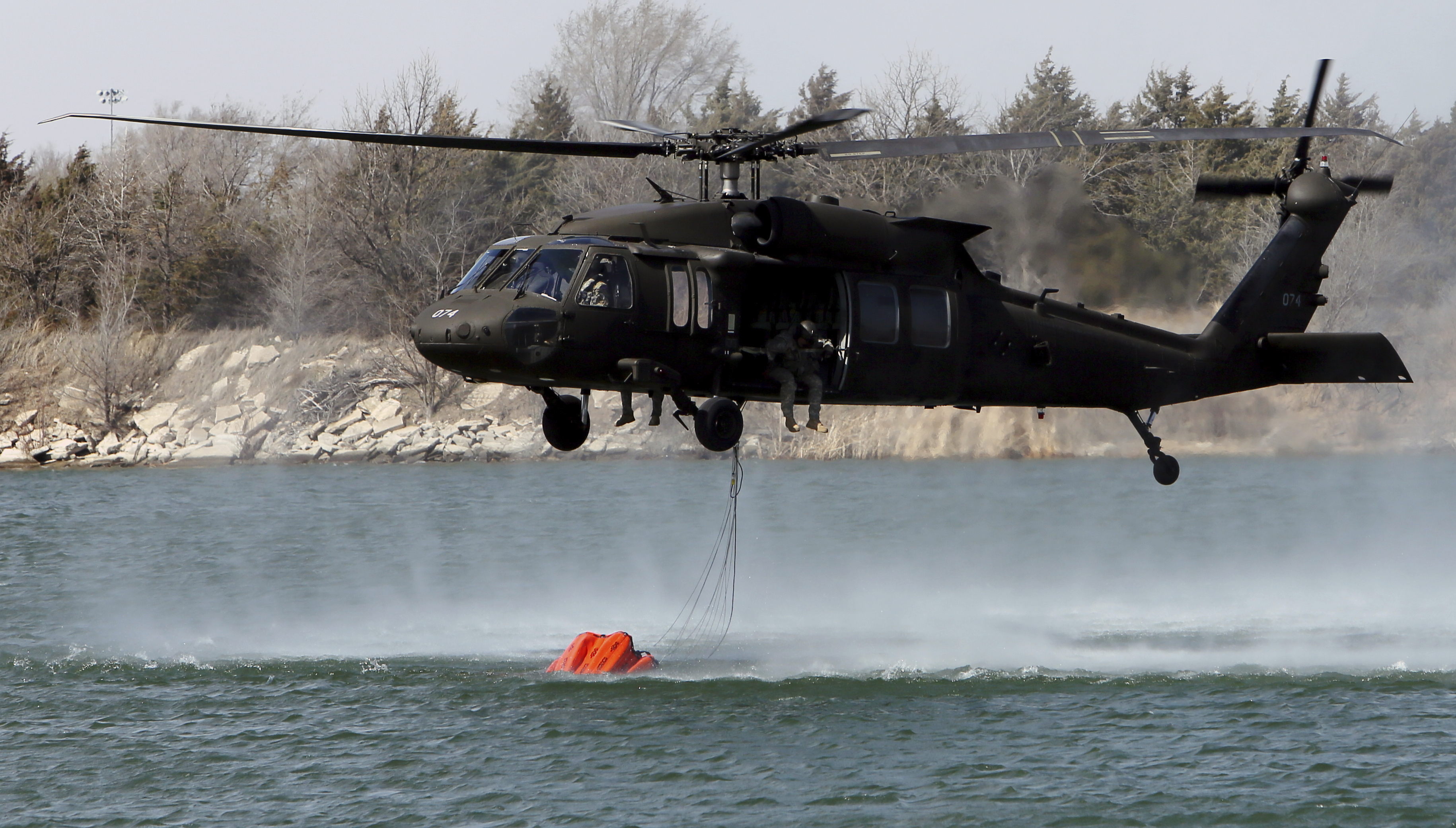 A National Guard helicopter picks up water from the Gravel & Concrete Inc. sandpit in Nickerson, Kan., on March 6, 2017. (Lindsey Bauman/The Hutchinson News via AP)