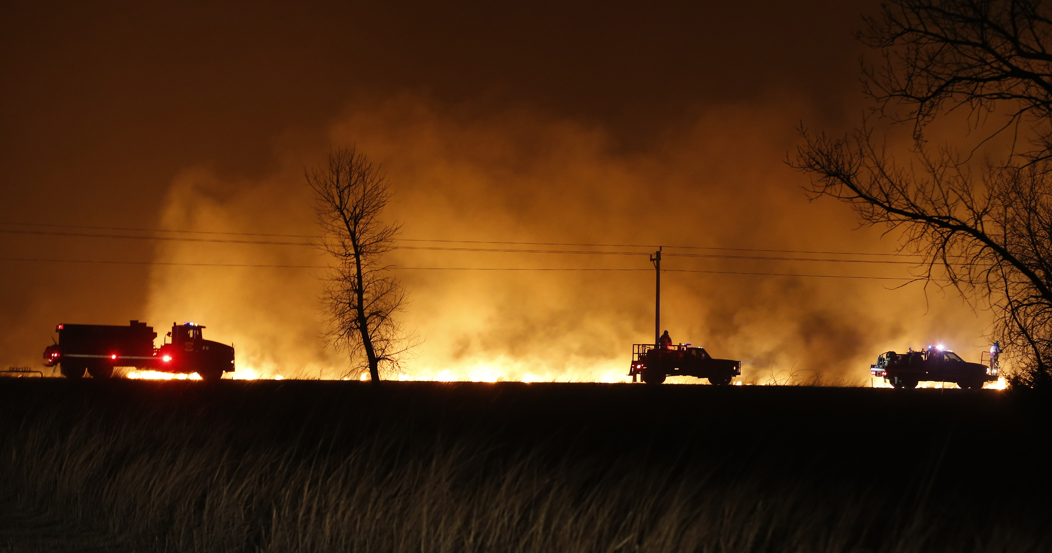 Firefighters from across Kansas and Oklahoma battle a wildfire near Protection, Kan., on March 6, 2017. (Bo Rader/The Wichita Eagle via AP)
