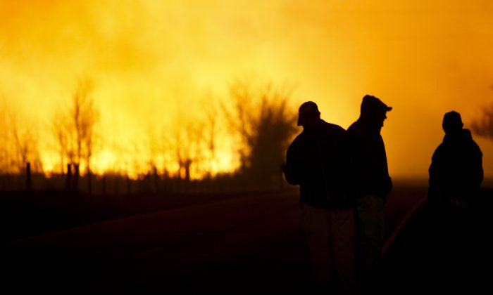 People are silhouetted against the orange glow of the fire as they watch a large grass fire burning out of control on , in the northeast of Hutchinson, Kan., March 6, 2017. (Lindsey Bauman/The Hutchinson News via AP)