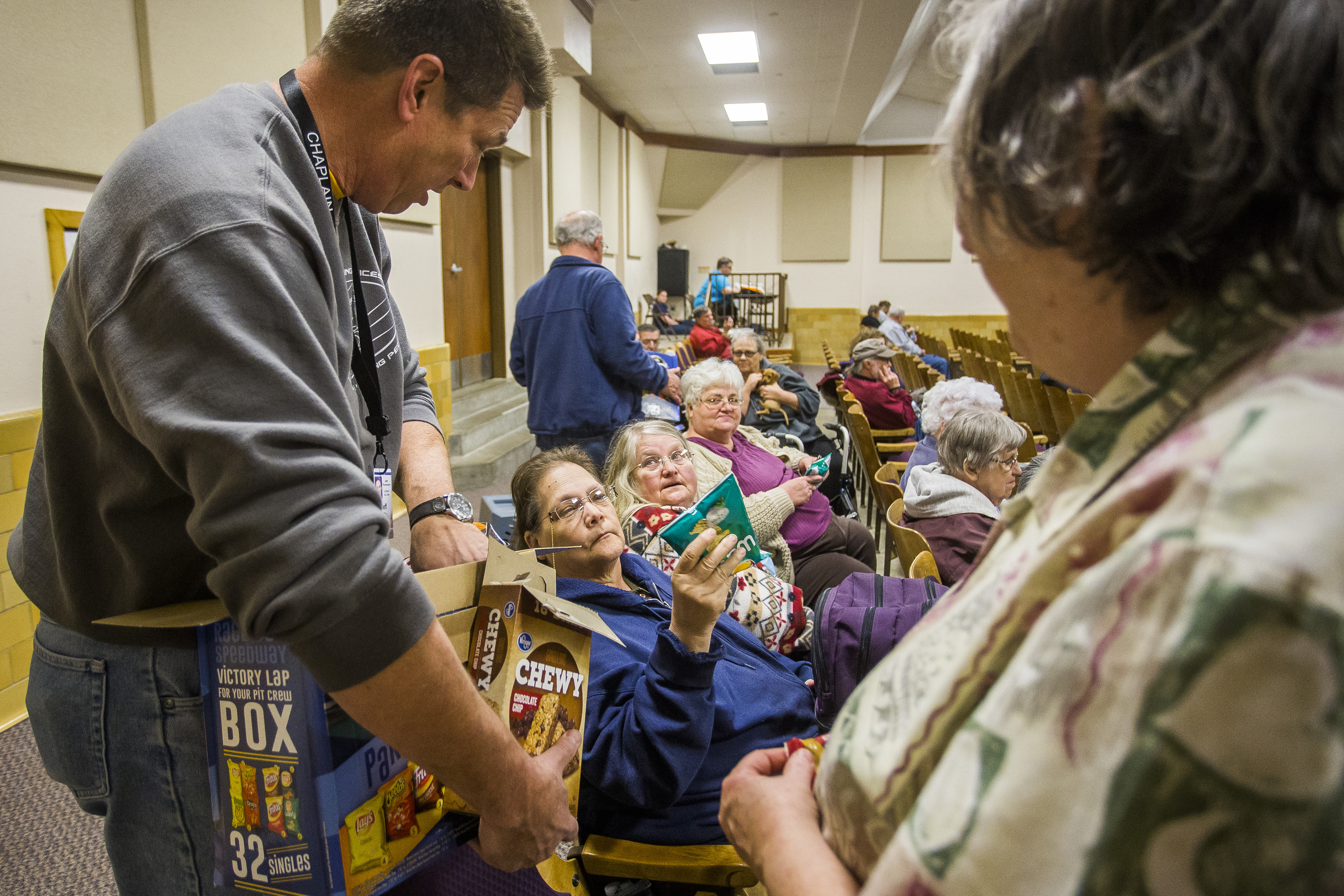 Southern Baptist Disaster Relief Chaplain Jeff Thompson passes bags of chips to (L-R) Suzanne Morgan, Carol Shaylor and Linda Nimmo inside an evacuation center at the Kansas State Fairgounds as a grassfire continues to rage north of Hutchinson, Kan., on March 6, 2017. (Katy Kildee/The Hutchinson News via AP)