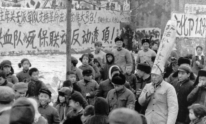"""A Chinese official is paraded through the streets of Beijing by Red Guards on Jan. 25, 1967. The words on his dunce cap accuses him of being a """"political pickpocket."""" During Mao Zedong's reign (1949-1977), many Chinese citizens and officials were accused of political crimes, and labeled """"class enemies"""" and """"counter-revolutionaries.""""  (Associated Press)"""