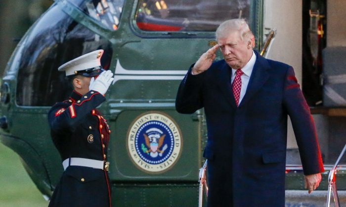 President Donald J. Trump (R) salutes as he disembarks Marine One on the South Lawn of the White House in Washington, DC. on March 5, 2017. (Lesser-Pool/Getty Images)