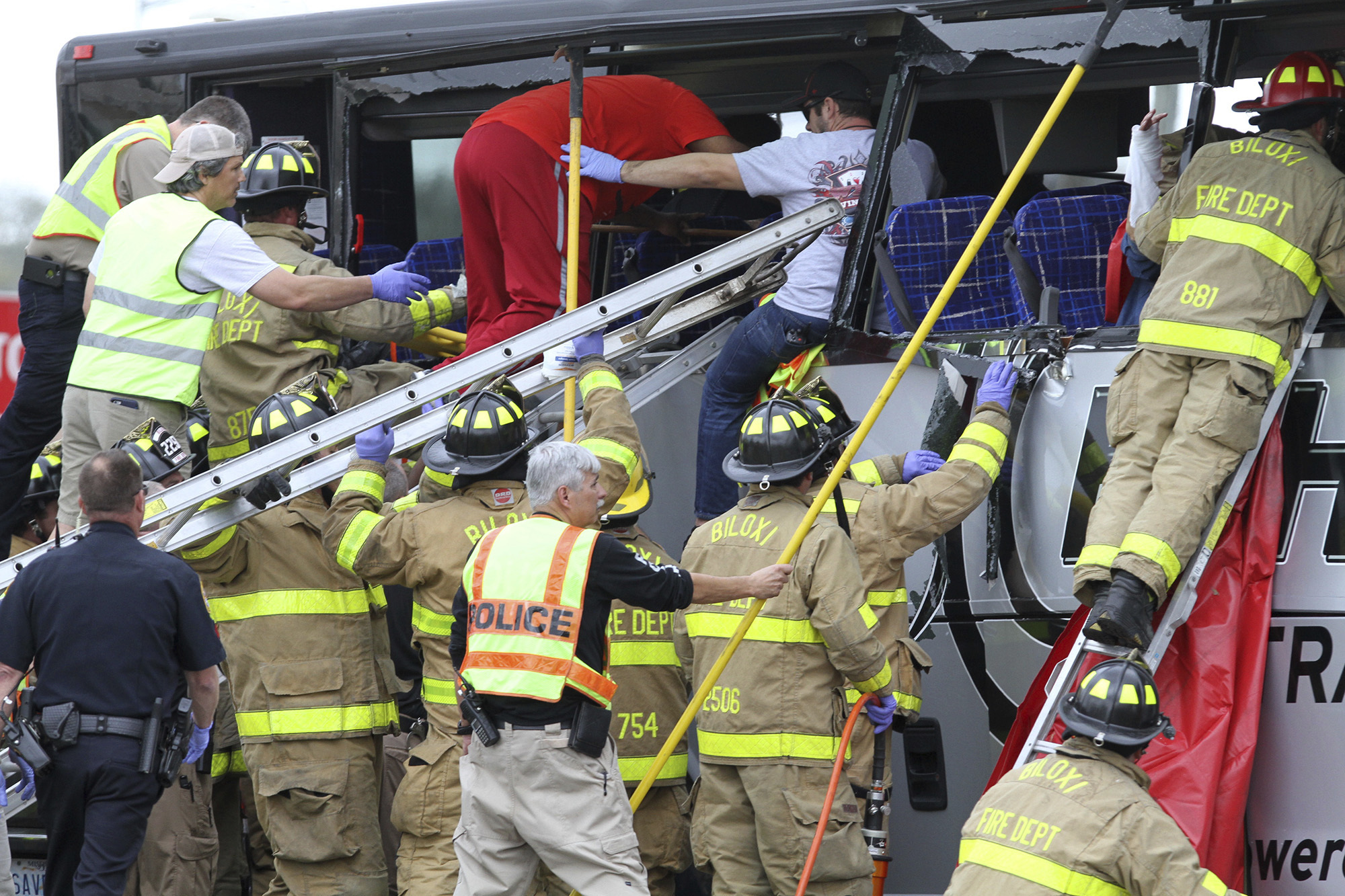 Rescue personnel work to remove passengers from a charter bus that was hit by a CSX train at the Main Street crossing in Biloxi, Miss., on March 7, 2017. ( John Fitzhugh/The Sun Herald via AP)
