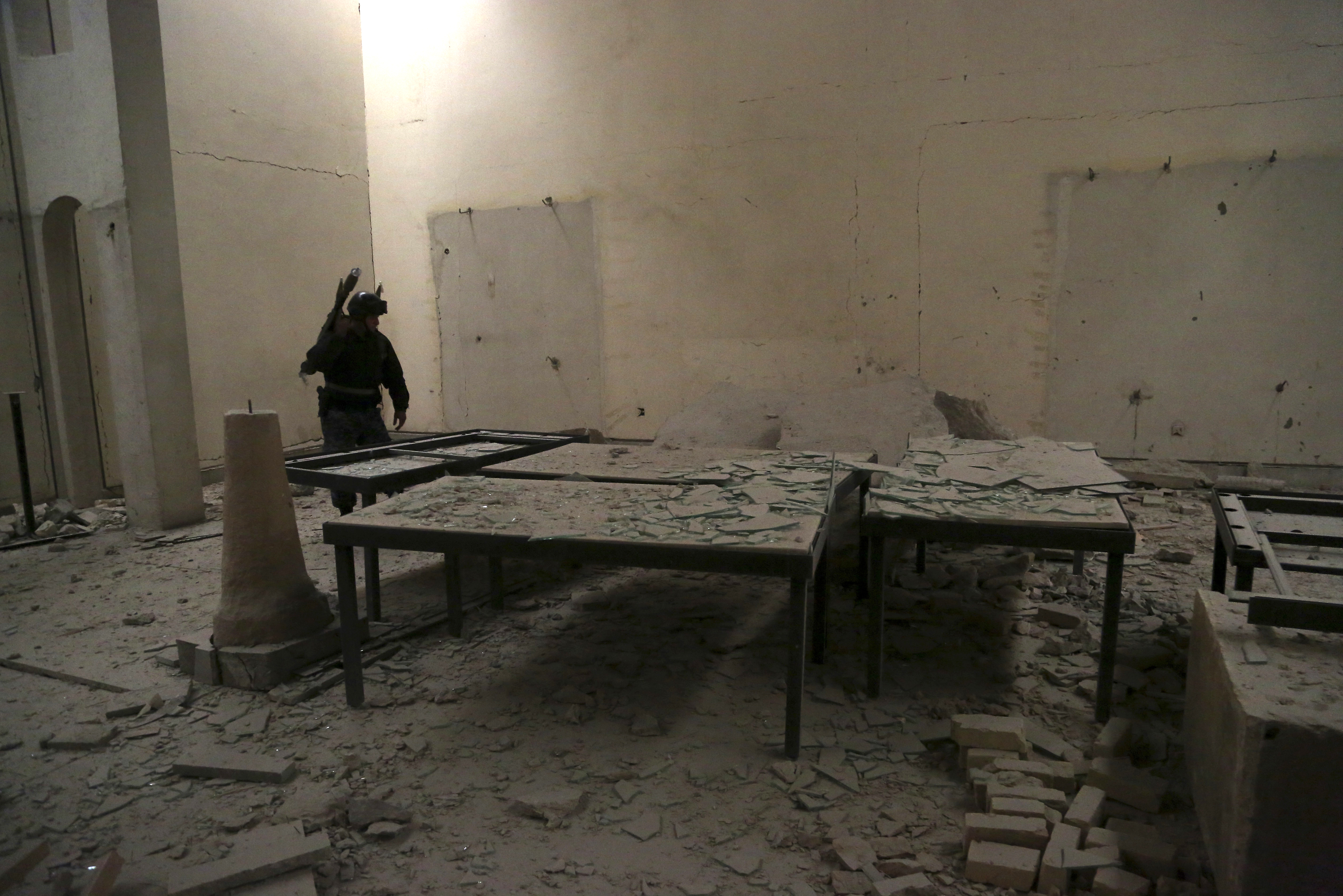An Iraqi federal policeman inspects the inside of Mosul's heavily damaged museum. (AP Photo/Khalid Mohammed)