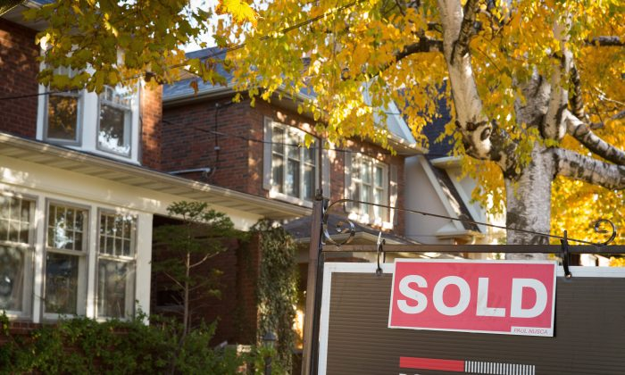 A real estate sold sign hangs in front of a west-end Toronto property on Nov. 4, 2016. Prices in Ontario's capital city continue to surge higher as the housing inventory dwindles. (The Canadian Press/Graeme Roy)