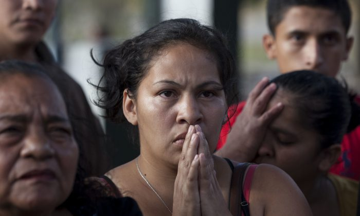 Relatives listen for new information about the injured after a fire, as they gather outside the children's shelter Virgin of the Assumption Safe Home, in San Jose Pinula, Guatemala on March 8, 2017. (AP Photo/Moises Castillo)