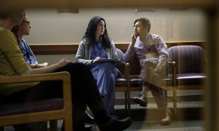 "Cambridge Hospital first-year residents Samantha Harrington (C) and Vikas Gampa (R) talk during ""sign-out"" at the hospital in Cambridge, Mass., on Feb. 27, 2017. (AP Photo/Steven Senne)"