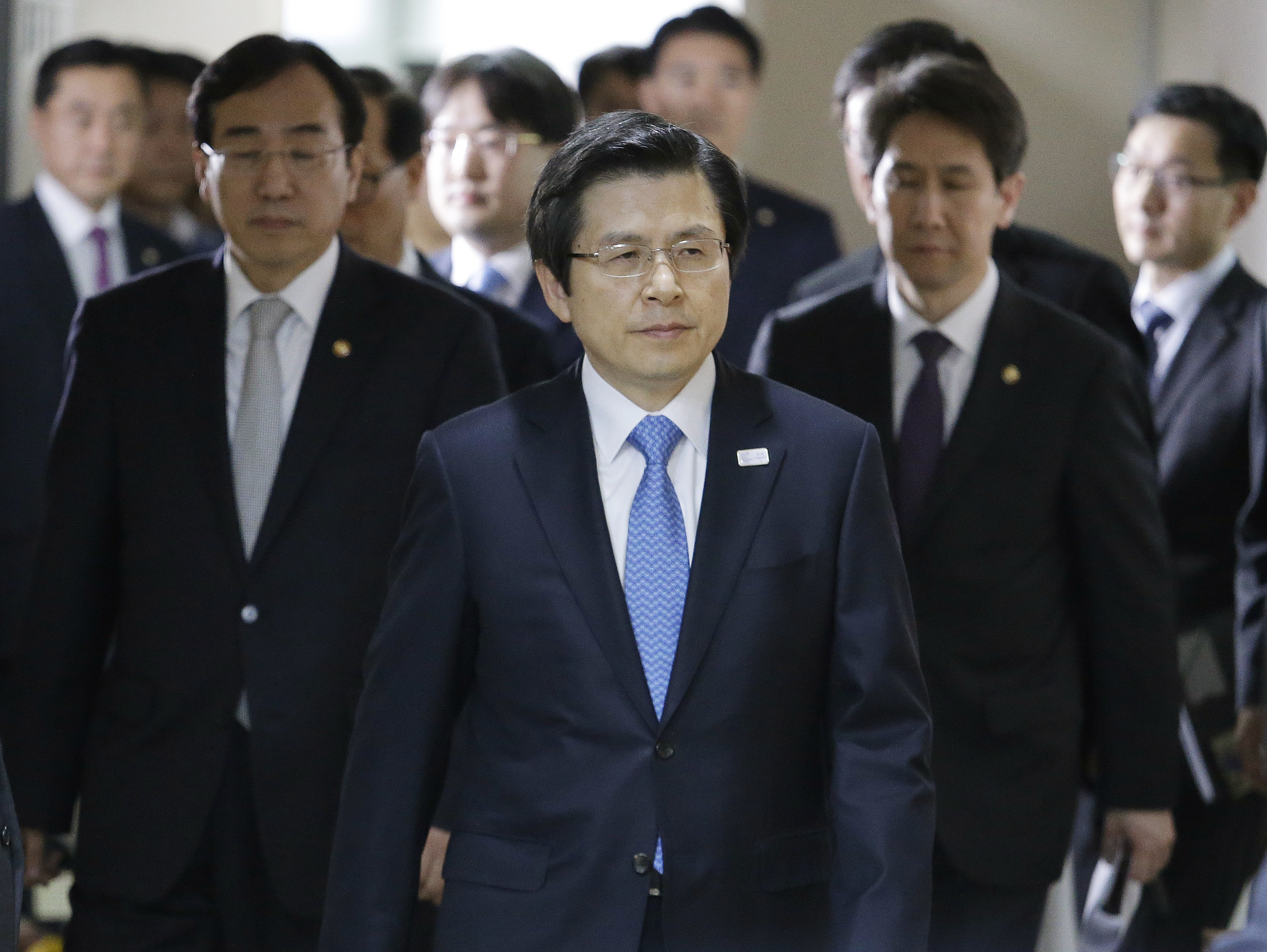 South Korean acting leader and Prime Minister Hwang Kyo-ahn, center, arrives to hold a press conference at the government complex in Seoul, South Korea on March 10, 2017. (AP Photo/Ahn Young-joon)