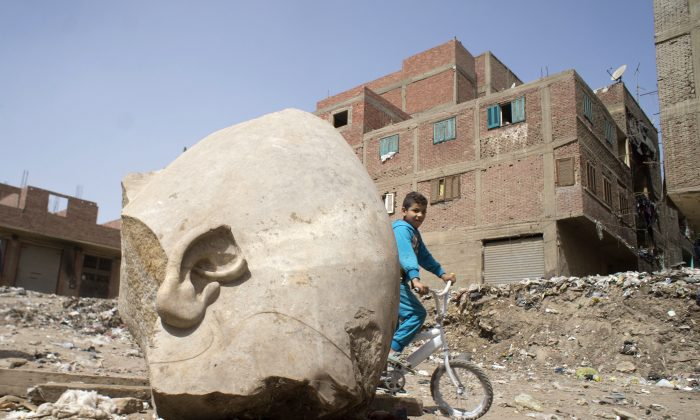 A boy rides his his bicycle past a recently discovered statue in a Cairo slum that may be of pharaoh Ramses II, in Cairo, Egypt on March 10, 2017. (AP Photo/Amr Nabil)
