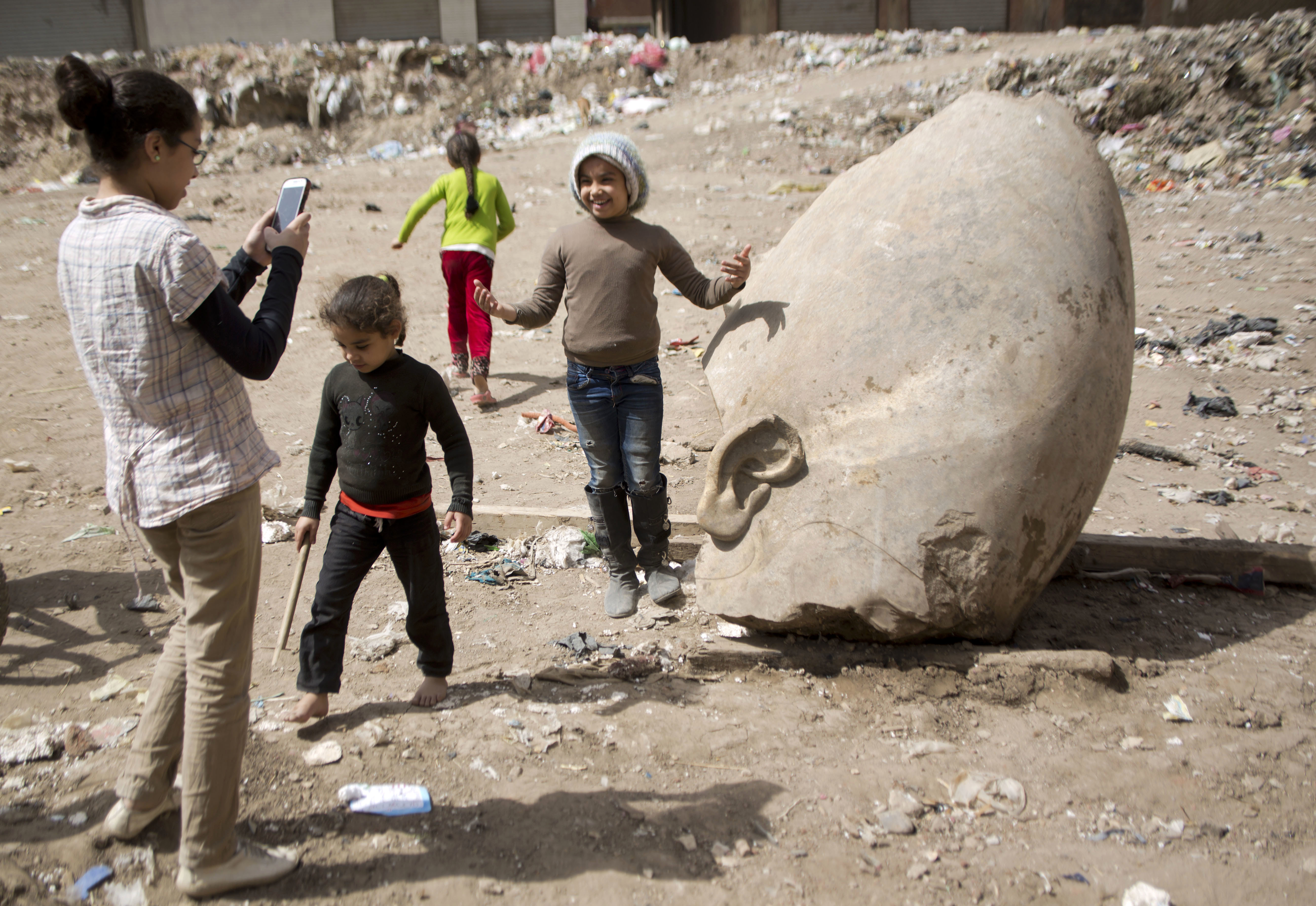 A child poses for a picture past a recently discovered statue in a Cairo slum that may be of pharaoh Ramses II, in Cairo, Egypt on March 10, 2017. (AP Photo/Amr Nabil)