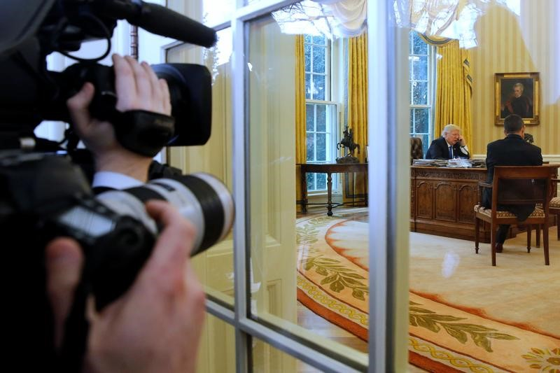 Photographers look on as U.S. President Donald Trump speaks by phone with Germany's Chancellor Angela Merkel in the Oval Office at the White House in Washington, U.S. Jan. 28, 2017. (REUTERS/Jonathan Ernst)
