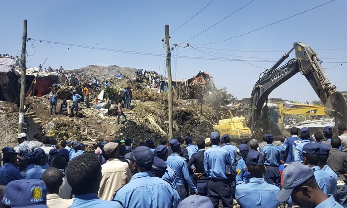 Police officers secure the perimeter at the scene of a garbage landslide, as excavators aid rescue efforts, on the outskirts of the capital Addis Ababa, Ethiopia on March 12, 2017. (AP Photo/Elias Meseret)