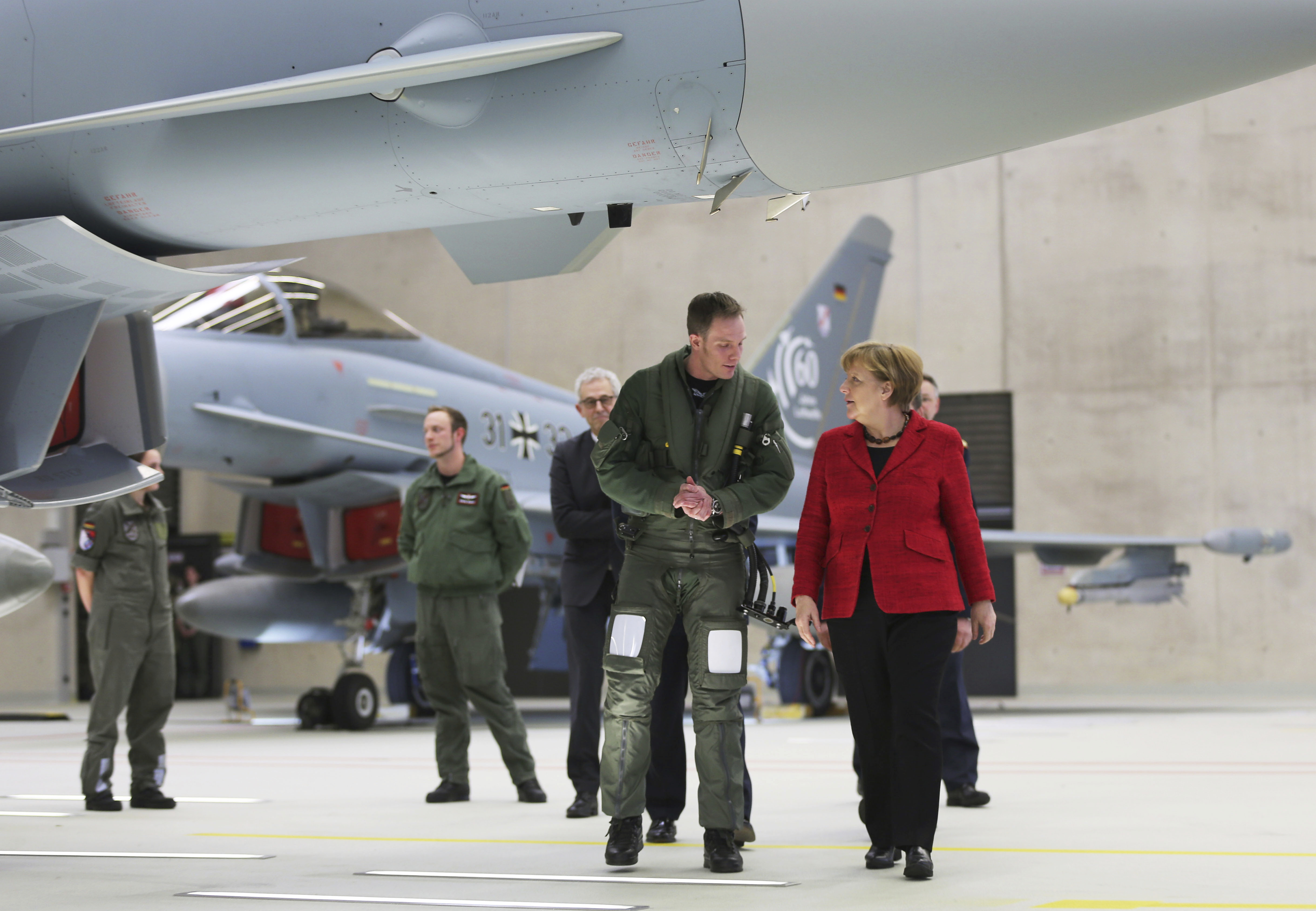 German Chancellor Angela Merkel speaks to pilot Patrick Betling (C) next to a Eurofighter in Noervenich, Germany on 21, 2016. (Oliver Berg//dpa via AP)