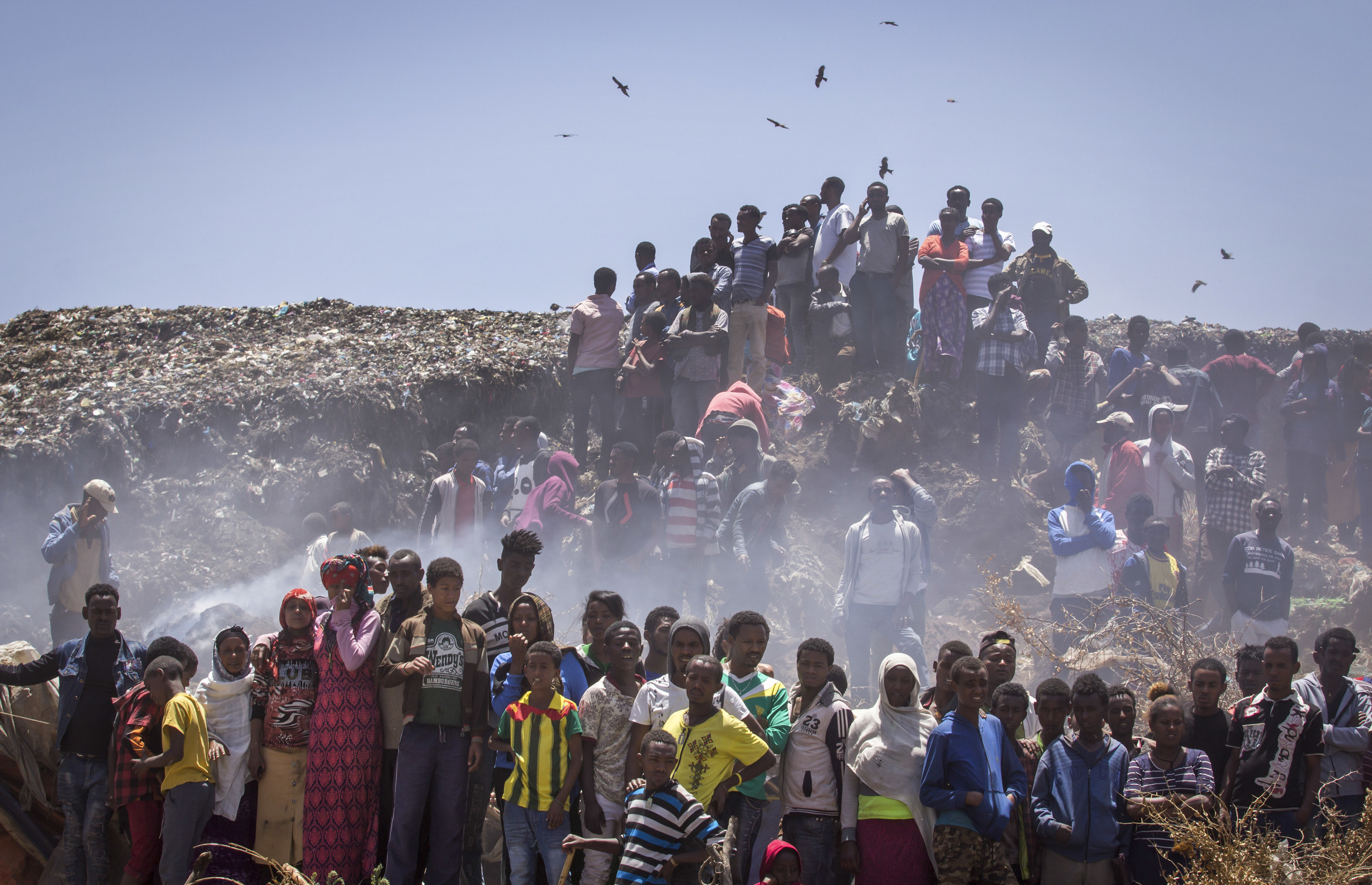 Residents look on as rescue efforts take place at the scene of a garbage landslide, on the outskirts of the capital Addis Ababa, in Ethiopia on March 12, 2017. (AP Photo/Mulugeta Ayene)