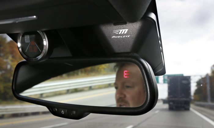 A Mobileye camera system that can be installed in your car to monitor speed limits and warn drivers of potential collisions, mounted behind the rearview mirror during a demonstration of the system, in Ann Arbor, Mich. on Oct. 14, 2015. (AP Photo/Carlos Osorio, File)