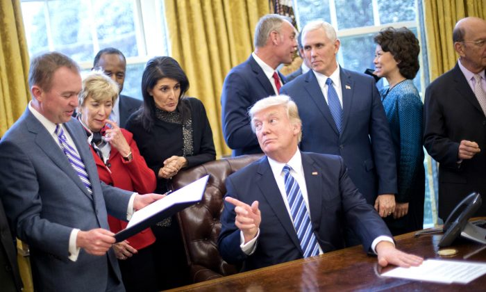 President Donald Trump looks over towards Budget Director Mick Mulvaney (L) after signing an executive order in the Oval Office of the White House in Washington on March 13, 2017. (AP Photo/Pablo Martinez Monsivais)