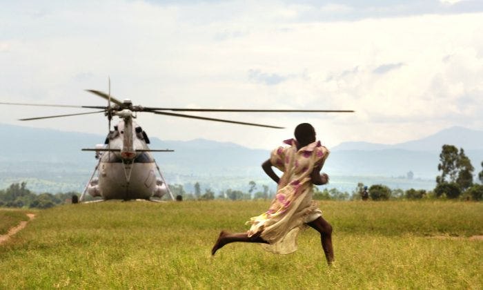 A girl runs as a UN helicopter lands at a refugee camp in Kiwanja, Democratic Republic of Congo on Nov. 07, 2008. (Uriel Sinai/Getty Images)
