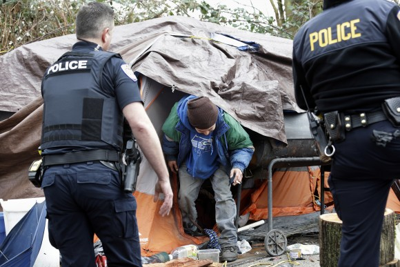 Leroy Henry (C) steps out of his tent in the woods to talk with police officer Kevin Davis, left, and Sgt. Mike Braley in Everett, Wash. on Feb. 16, 2017. As overdose deaths from opioids and heroin spiked the mayor of Everett took steps to tackle the epidemic devastating this working-class city north of Seattle. Mayor Ray Stephanson has spent thousands to clean up streets, hire social workers to ride along with police officers and build permanent housing for the chronically homeless. (AP Photo/Elaine Thompson)