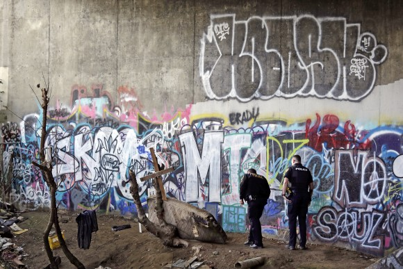 Police Sgt. Mike Braley, left, and officer Kevin Davis walk along the bottom of a highway overpass, a known location for drug use, to check for anyone living there in Everett, Wash. on Feb. 16, 2017. (AP Photo/Elaine Thompson)