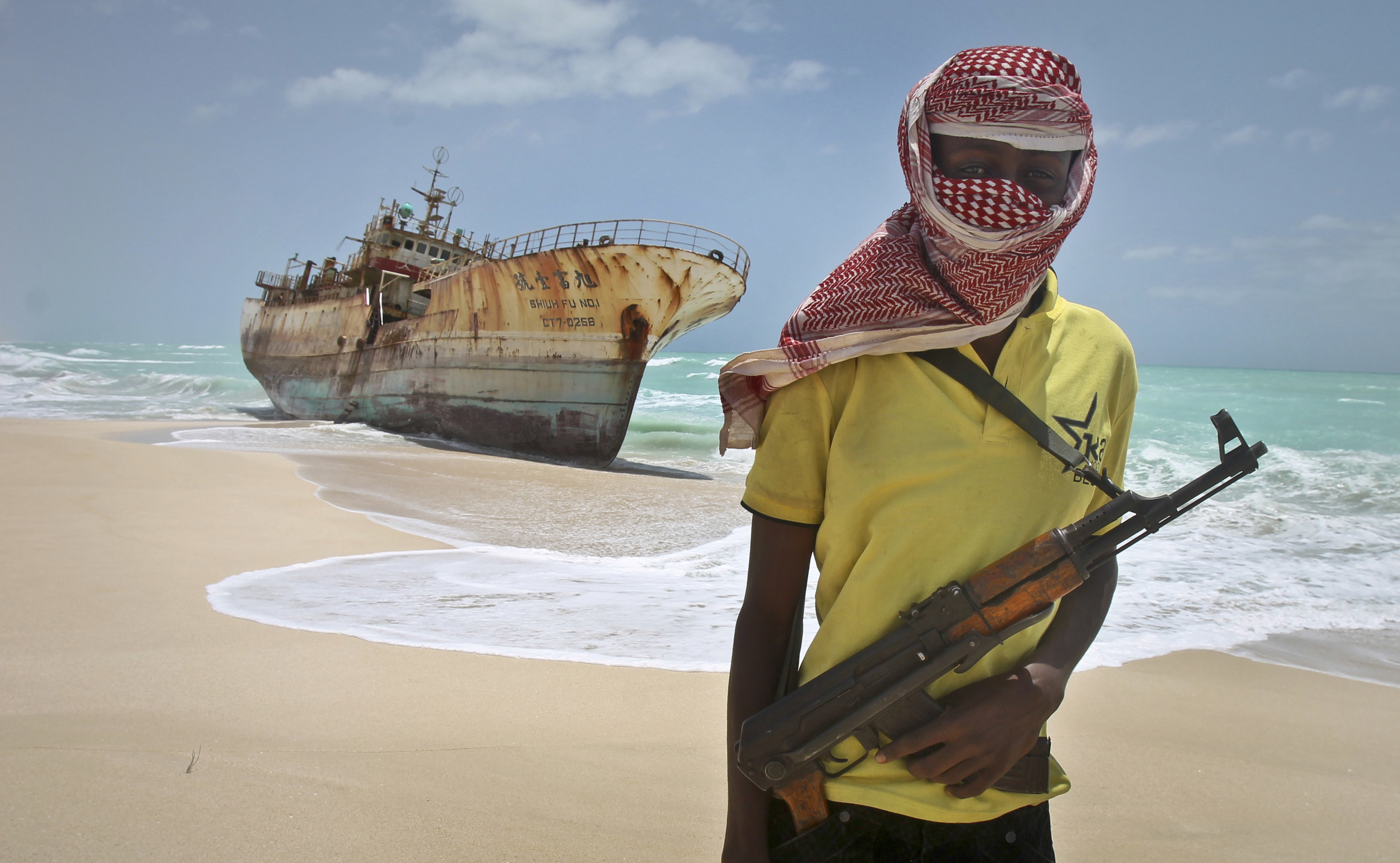 Masked and armed Somali pirate Hassan stands near a Taiwanese fishing vessel washed ashore after the pirates were paid a ransom and the crew were released in the once-bustling pirate den of Hobyo, Somalia on Sept. 23, 2012. (AP Photo/Farah Abdi Warsameh)