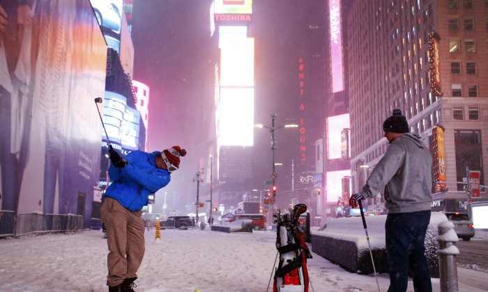 Two men play golf with a tennis ball as a snowstorm sweeps through Times Square on in New York on March 14, 2017. (AP Photo/Mark Lennihan)