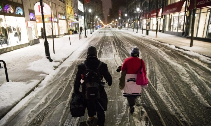 A couple walks in the street during a winter storm in Philadelphia on March 14, 2017. (AP Photo/Matt Rourke)