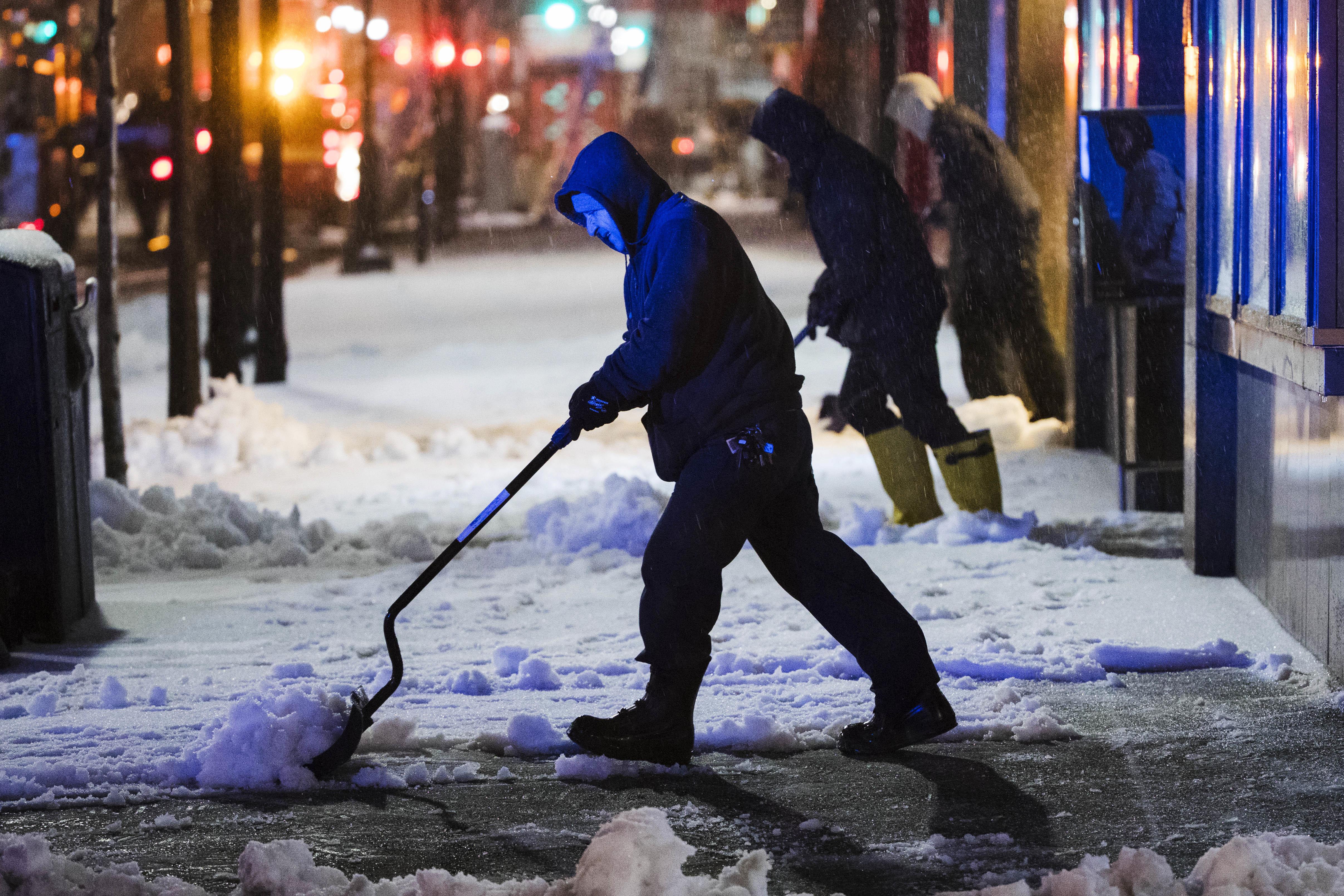 Workmen clear a sidewalk during a winter storm in Philadelphia on March 14, 2017. (AP Photo/Matt Rourke)