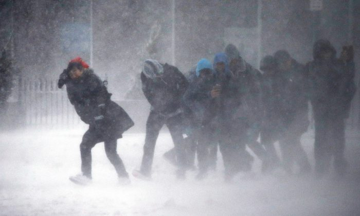 People struggle to walk in the blowing snow during a winter storm Tuesday, March 14, 2017, in Boston. (AP Photo/Michael Dwyer)