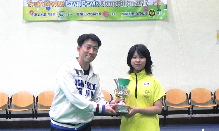 HAPPY GIRL – Thirteen years old Tam Wing Chui, the first girl winner of the Youth Novice Singles competition last Sunday, Mar 14, receives her trophy from Mr Gordon Lui of LCSD. (Howard Poon)
