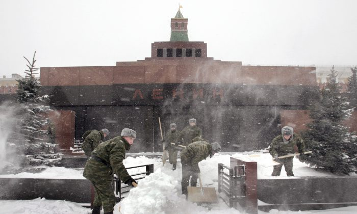 Russian soldiers clear snow from an area in front of former Russian communist leader Vladimir Ilyich Lenin's Mausoleum on Moscow's Red Square on Jan. 28 2005. Nearly a century after Lenin's death, his embalmed body lays in the mausoleum on the Red Square. (YURI KADOBNOV/AFP/Getty Images)