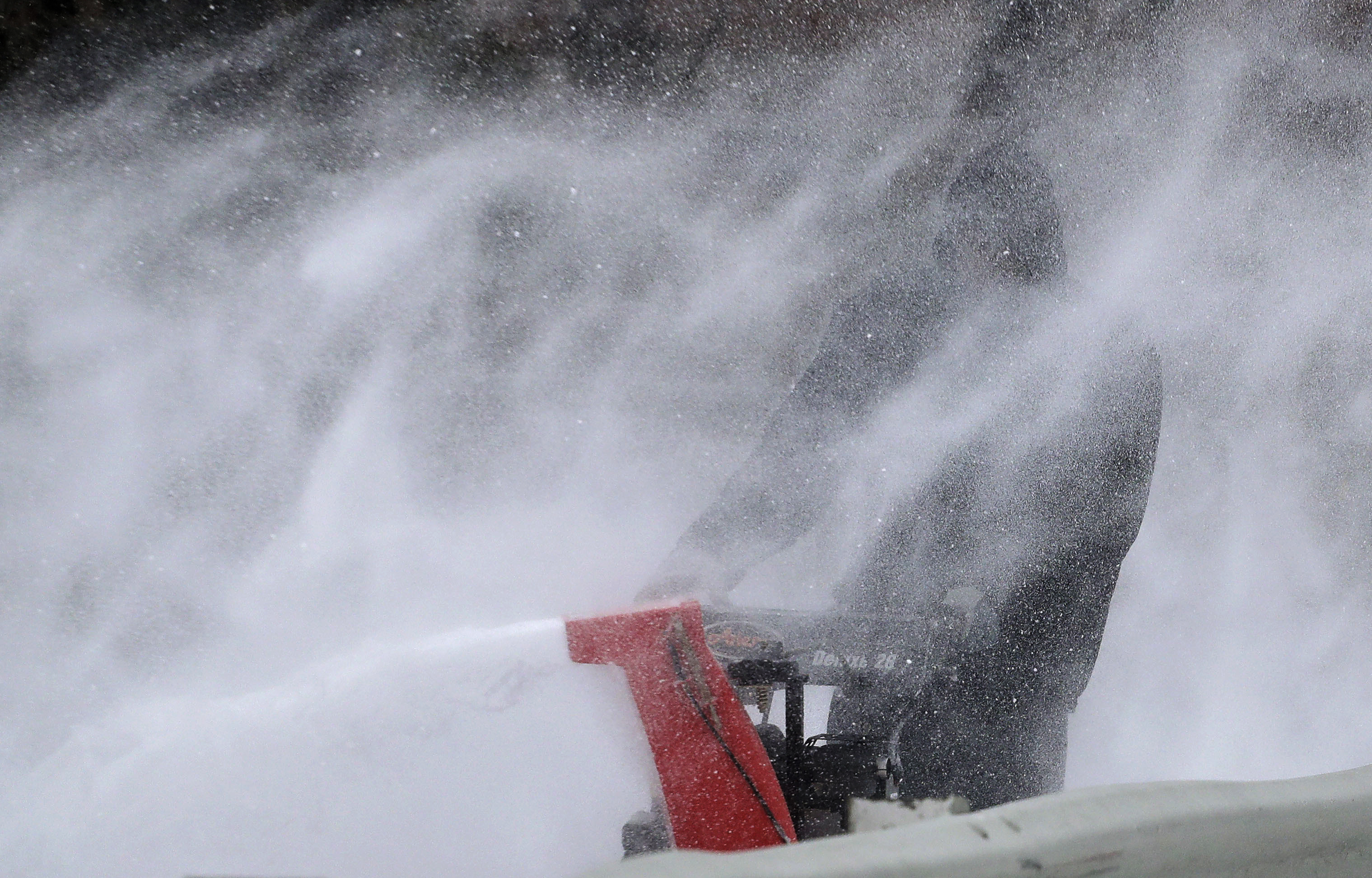 A gust of wind blows snow back at Roger Lane, a custodian at Yonkers Public School 17, as he clears a sidewalk in front of the school with a snow blower during a snow storm in New York on March 14, 2017. (AP Photo/Julie Jacobson)