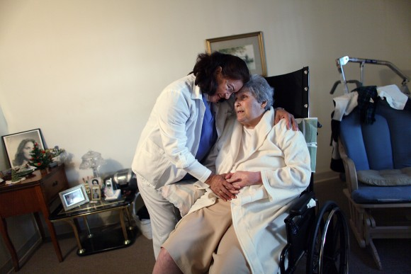 Hhome health aide Wendy Cerrato hugs Olga Socarras as she helps her during a visit in Miami in this file photo.  (Joe Raedle/Getty Images)