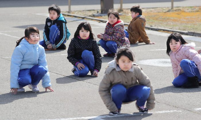 Elementary school students squat down on the street as they participate in an evacuation drill for local residents based on the scenario that a ballistic missile launched landed in Japanese waters, in Oga, Akita prefecture, Japan March 17, 2017. Kyodo/via REUTERS)