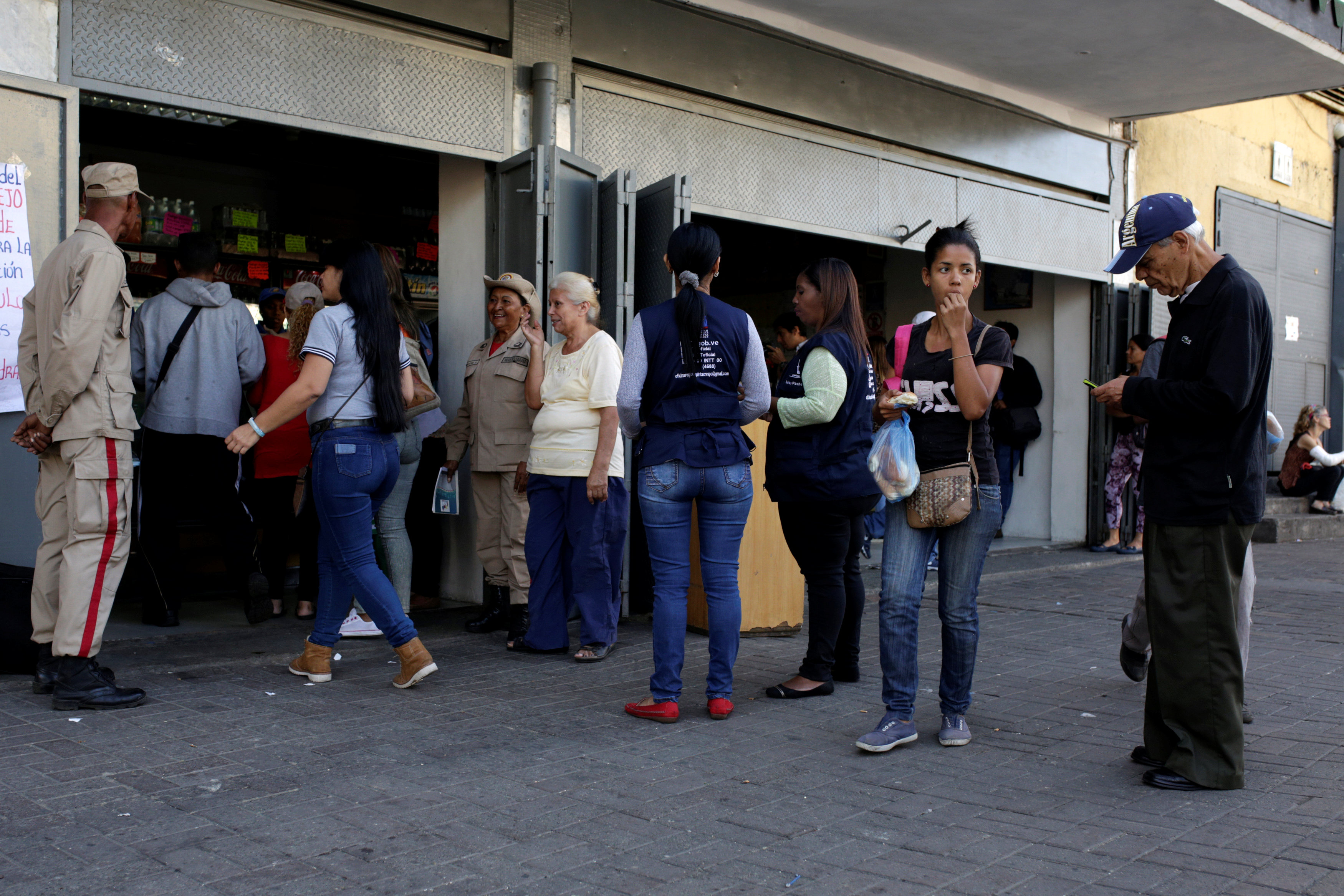 Militia officers stand guard at the entrance of a bakery as people line up to buy bread in Caracas, Venezuela on March 17, 2017. (REUTERS/Marco Bello)
