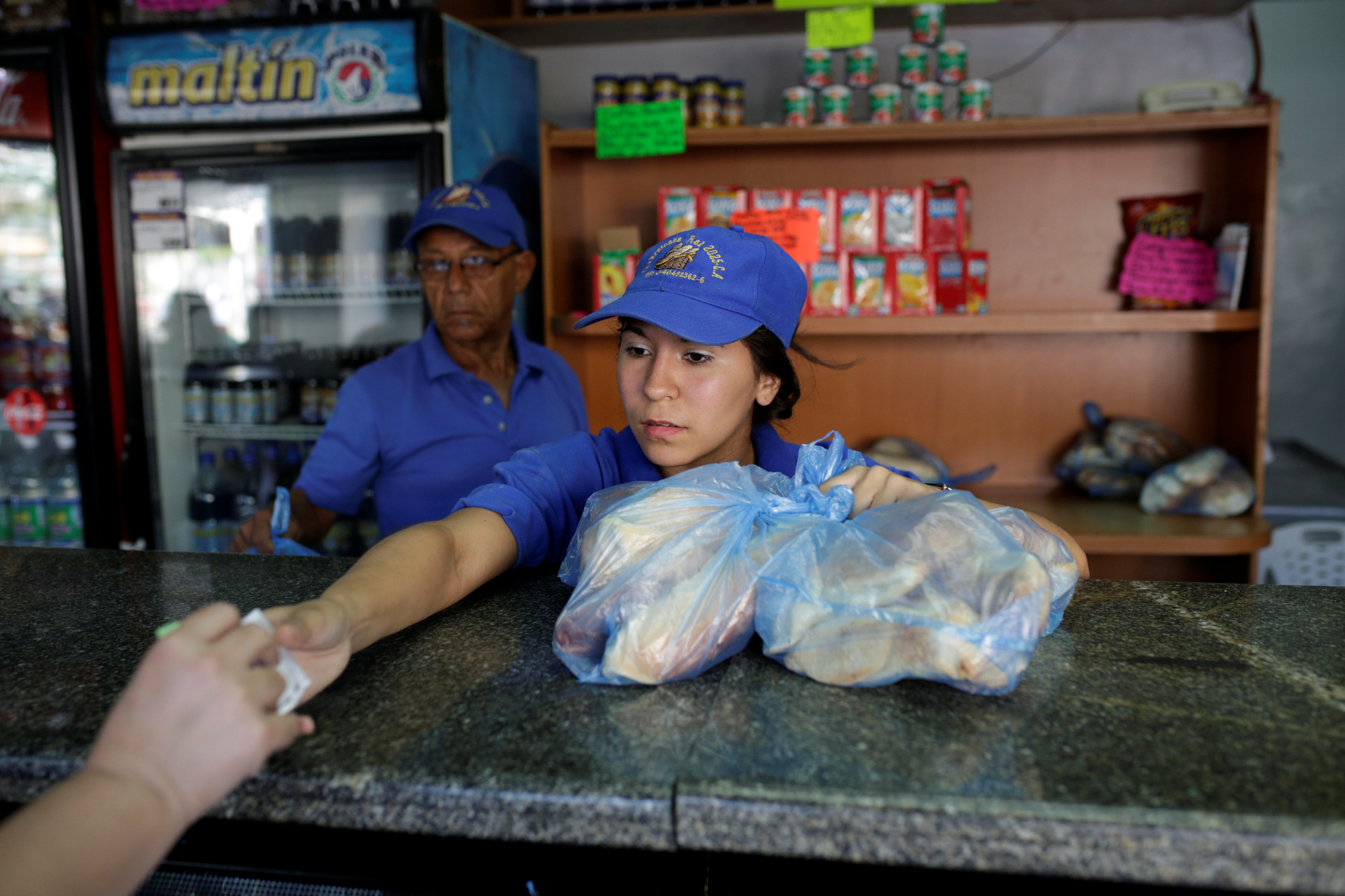 A saleswoman sells bread at a bakery in Caracas, Venezuela on March 17, 2017. (REUTERS/Marco Bello)