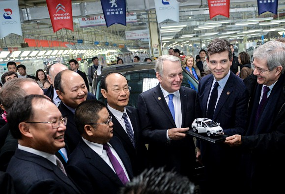 Then-French Prime Minister Jean-Marc Ayrault (3rd R) prepares to present a model car to Chinese managers on a visit to the Dongfeng Peugeot-Citroën Automobile plant on Dec. 7, 2013 in Wuhan,China. The following year, Chinese state-owned Dongfeng became an equal shareholder in PSA Peugeot Citroën, the leading carmaker in France. (PETER PARKS/AFP/Getty Images)