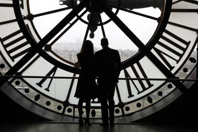 Britain's Prince William, Duke of Cambridge, and his wife Britain's Kate, Duchess of Cambridge, look at the Seine river through a giant clock at the Musee d'Orsay museum -the former Gare d'Orsay train station- during their visit to the museum on March 18. (Francois Guillot/Pool Photo via AP)
