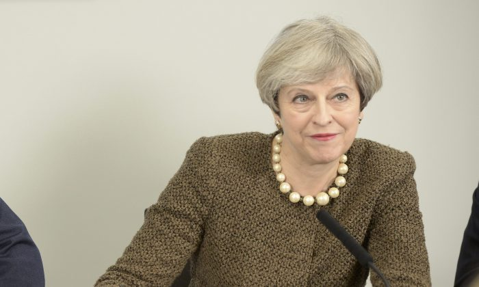 Britain's Prime Minister Theresa May signs a Swansea City deal during a meeting at the Liberty Stadium in Swansea on March 20, 2017. (REUTERS/Ben Birchall/Pool)