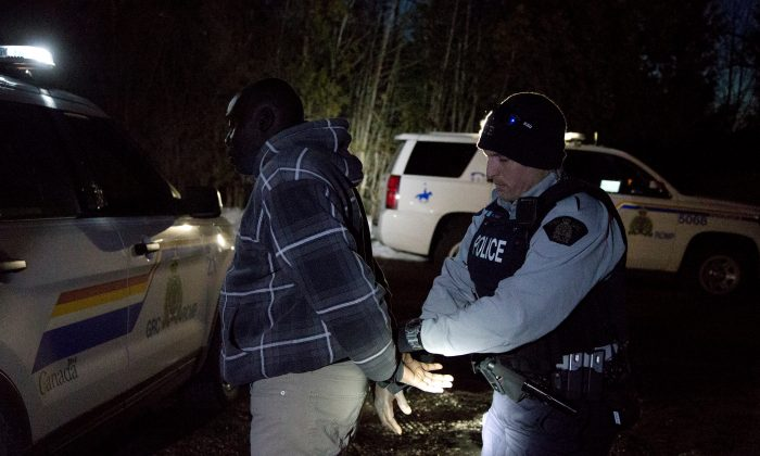 A man who claimed to be from Sudan is handcuffed by a Royal Canadian Mounted Police (RCMP) officer after he illegally crossed the U.S.-Canada border leading into Hemmingford, Quebec, Canada on March 20, 2017. (REUTERS/Christinne Muschi)